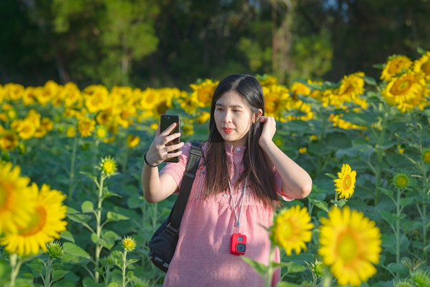 Zwangere vrouw in een zonnebloem veld