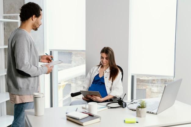 Zwangere vrouw in gesprek met haar collega