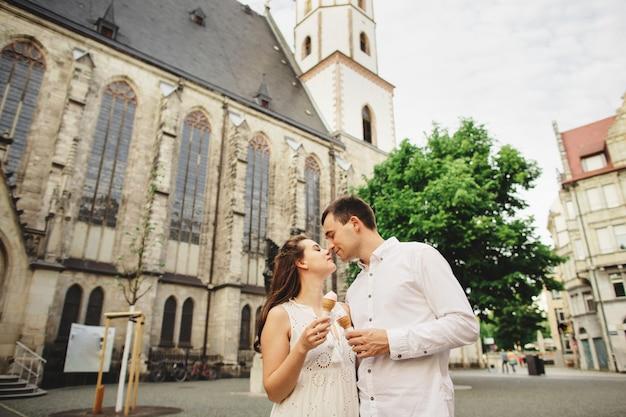 Zwangere vrouw in jurk en haar man genieten van wandelen in de oude stad