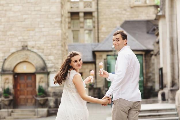Zwangere vrouw in jurk en haar man lopen in de stad