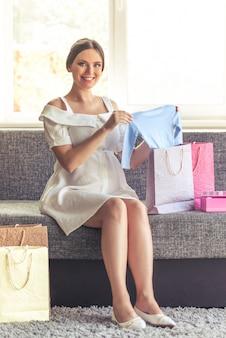 Zwangere vrouw in jurk houdt schattige babykleding.