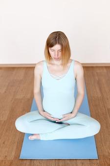 Zwangere vrouw in lotushouding op een sportmat mediteren