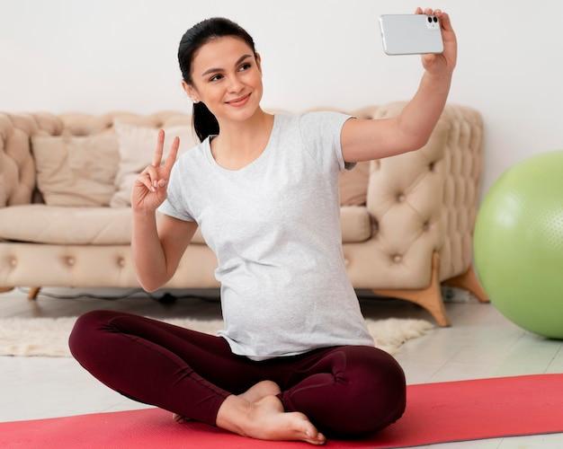 Zwangere vrouw in lotuspositie die een selfie neemt