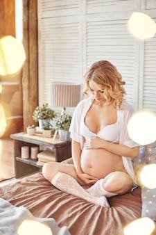 Zwangere vrouw in ondergoed op mijn bed. blonde vrouw bereidt zich voor om een moeder te worden. bevalling, het geluk van een vrouw. sexy zwangere vrouw in wit ondergoed