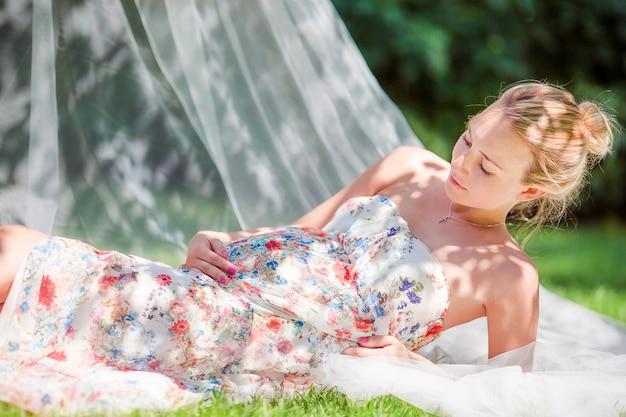 Zwangere vrouw in openlucht park, warm weer