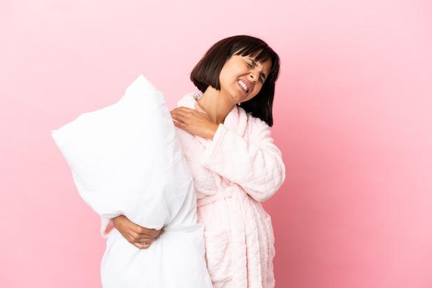 Zwangere vrouw in pyjama geïsoleerd op roze achtergrond die lijdt aan pijn in de schouder omdat ze moeite heeft gedaan