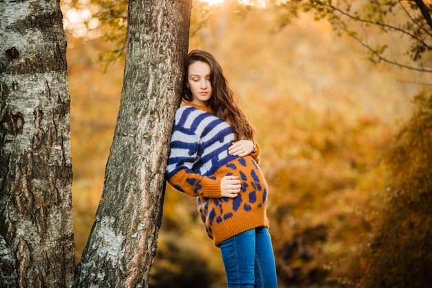 Zwangere vrouw in trui in de herfst voor een wandeling