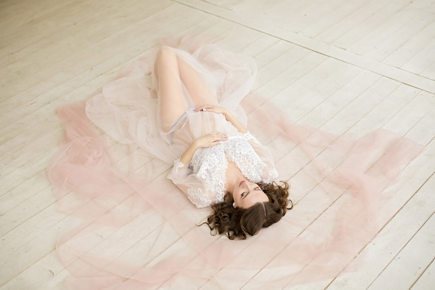Zwangere vrouw in wit op vloer