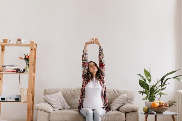 Zwangere vrouw in witte tee en geruite overhemd strekt zich uit