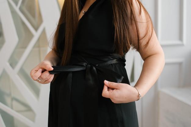 Zwangere vrouw in zwarte jurk bindt een strik op haar jurk