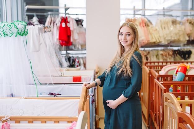 Zwangere vrouw kiest een babybedje in de winkel.