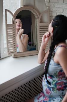 Zwangere vrouw kijkt de spiegel make-up op te zetten