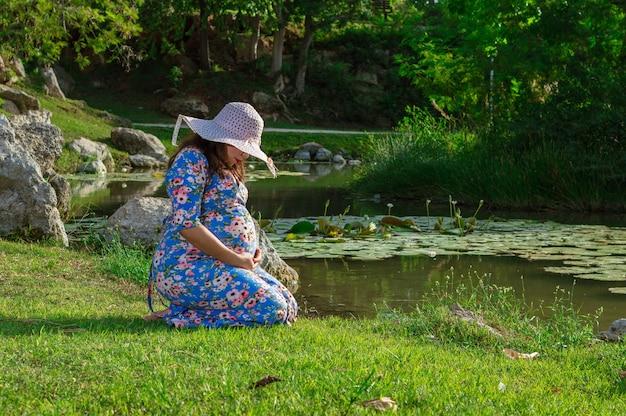 Zwangere vrouw kijkt naar haar buik geknield op gras in de buurt van meer