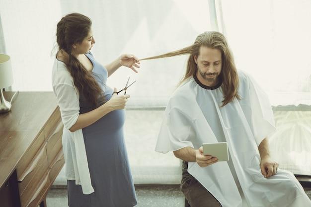 Zwangere vrouw krijgt een knipbeurt voor echtgenoot terwijl ze thuis blijft als mooie warme en liefdevolle familiemoment vintage kleurtint.