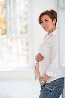 Zwangere vrouw luistert liefdevol naar baby in haar buik