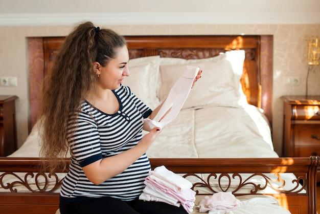 Zwangere vrouw maakt zich klaar voor het kraamkliniek, babyspullen inpakken. zwangerschap, geboorteconcept.