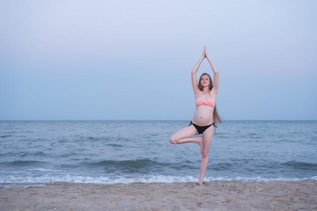 Zwangere vrouw mediteert op het strand