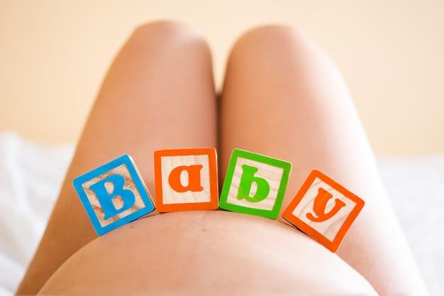 Zwangere vrouw met babywoord op haar buik