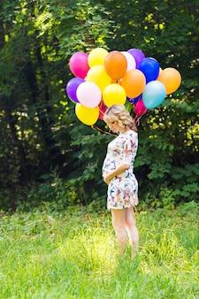 Zwangere vrouw met ballonnen buitenshuis