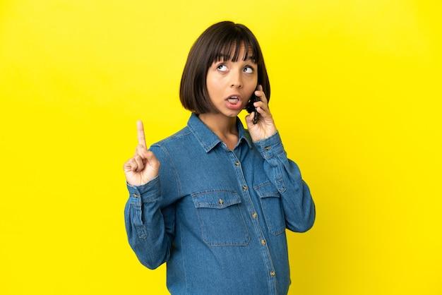 Zwangere vrouw met behulp van mobiele telefoon geïsoleerd op gele achtergrond denken een idee met de vinger omhoog