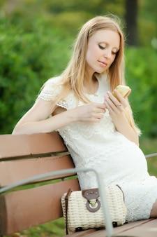 Zwangere vrouw met behulp van mobiele telefoon