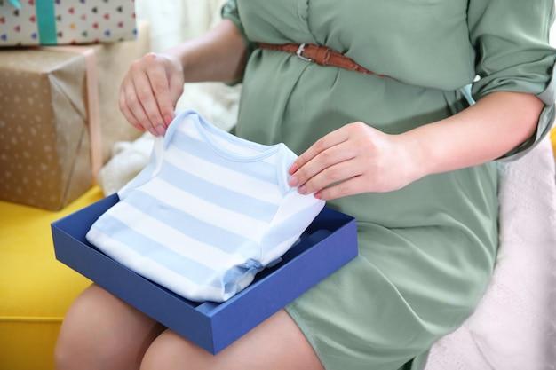 Zwangere vrouw met cadeautjes op baby shower feestje