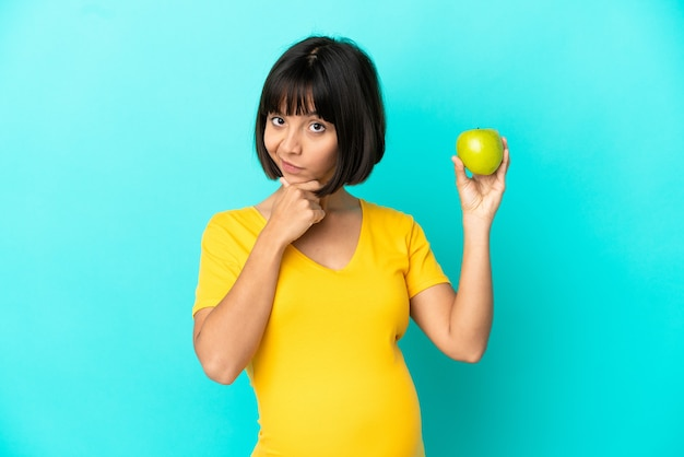 Zwangere vrouw met een appel geïsoleerd op blauwe achtergrond denken
