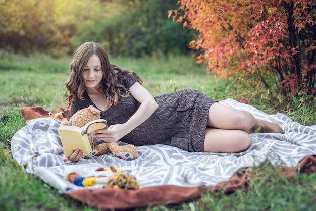 Zwangere vrouw met een buik ligt op een deken en het lezen van verhalen aan de baby.