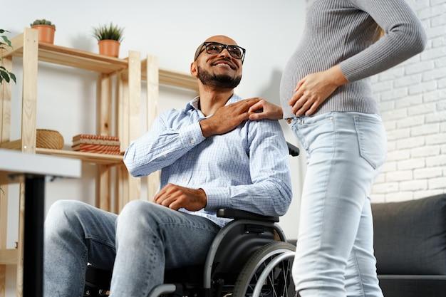 Zwangere vrouw met een hand van haar gehandicapte echtgenoot die in een rolstoel zit