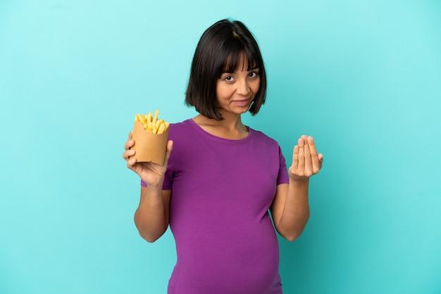 Zwangere vrouw met gebakken chips over geïsoleerde achtergrond uitnodigend om met de hand te komen. blij dat je gekomen bent