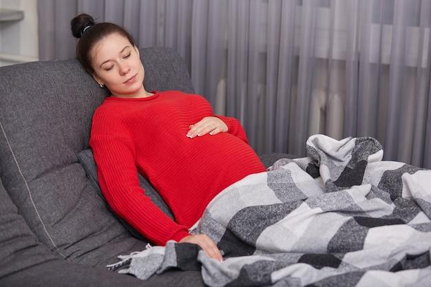Zwangere vrouw met grote buik, draagt rode trui, slaapt op bank, bedekt met plaid, geniet van huiselijke sfeer, heeft goede rust