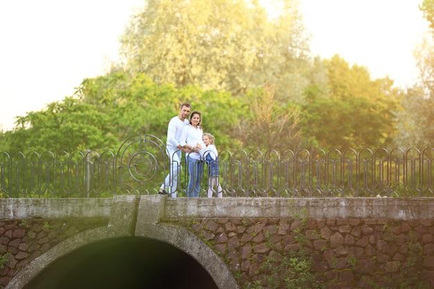 Zwangere vrouw met haar dochter en echtgenoot in het park op de brug
