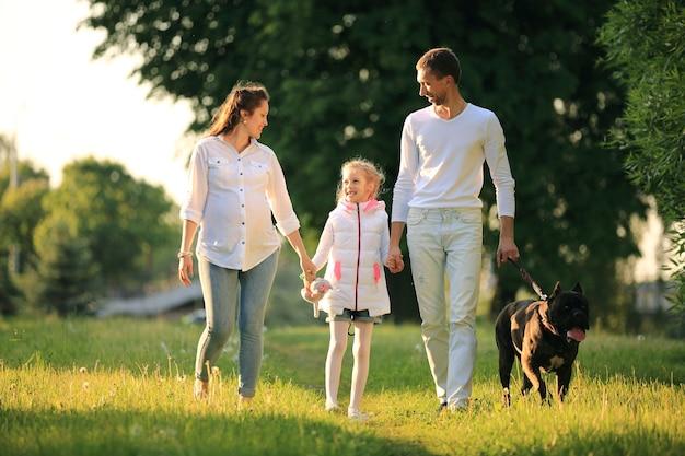 Zwangere vrouw met haar dochter en echtgenoot op een wandeling in het park op een zonnige dag