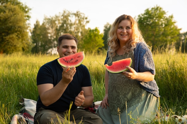 Zwangere vrouw met haar echtgenoot op een veld met bloemen.