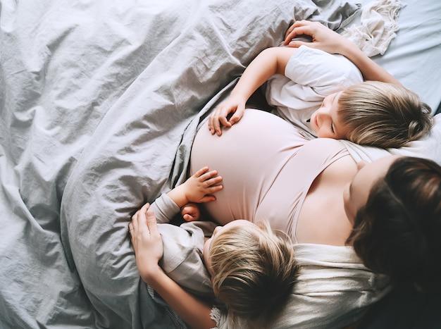 Zwangere vrouw met haar kinderen ontspannen in bed liefhebbende moeder en peuters samen thuis