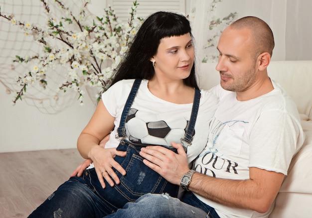 Zwangere vrouw met haar liefhebbende echtgenoot in een gelukkige afwachting van de baby