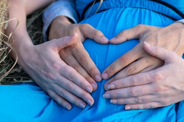 Zwangere vrouw met haar man handen op haar buik, concept van wachten op een kind, jonge ouders, zorg en liefde, moeder en vader. detailopname