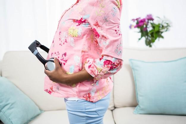 Zwangere vrouw met hoofdtelefoon op buik op de bank