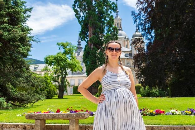 Zwangere vrouw met jurk en zonnebril poseren in het paleis van la granja de san idelfonso.