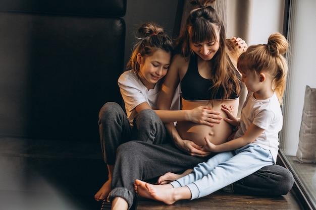 Zwangere vrouw met kinderen die bij het venster zitten