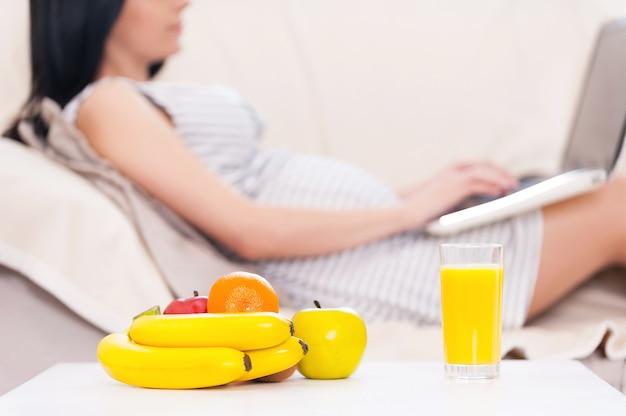 Zwangere vrouw met laptop. mooie zwangere vrouw die op laptop werkt terwijl ze op een bank ligt