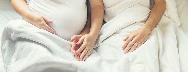 Zwangere vrouw met man omhelzingsbuik in bed. selectieve aandacht.