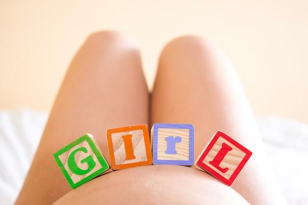 Zwangere vrouw met meisjeswoord op haar buik