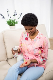 Zwangere vrouw met pillen en glas water op de bank