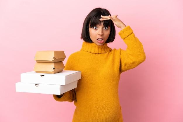 Zwangere vrouw met pizza's en hamburgers geïsoleerd op een roze achtergrond die een verrassingsgebaar doet terwijl ze naar de zijkant kijkt