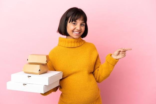Zwangere vrouw met pizza's en hamburgers geïsoleerd op een roze achtergrond die met de vinger naar de zijkant wijst