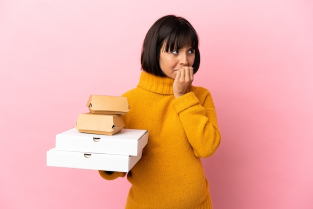 Zwangere vrouw met pizza's en hamburgers geïsoleerd op roze achtergrond met twijfels