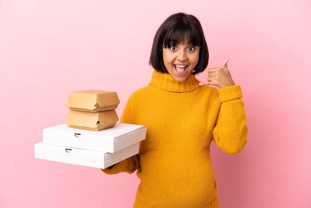 Zwangere vrouw met pizza's en hamburgers geïsoleerd op roze achtergrond telefoon gebaar maken. bel me terug teken