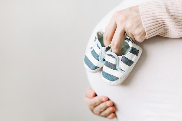 Zwangere vrouw met schoenen voor de pasgeboren baby