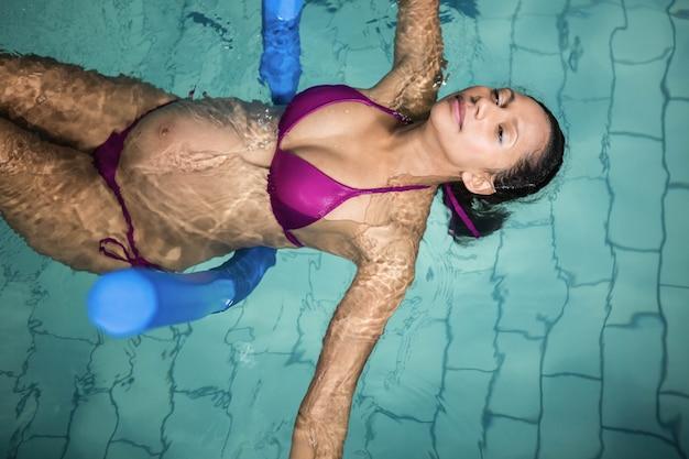 Zwangere vrouw met schuimrol in het zwembad